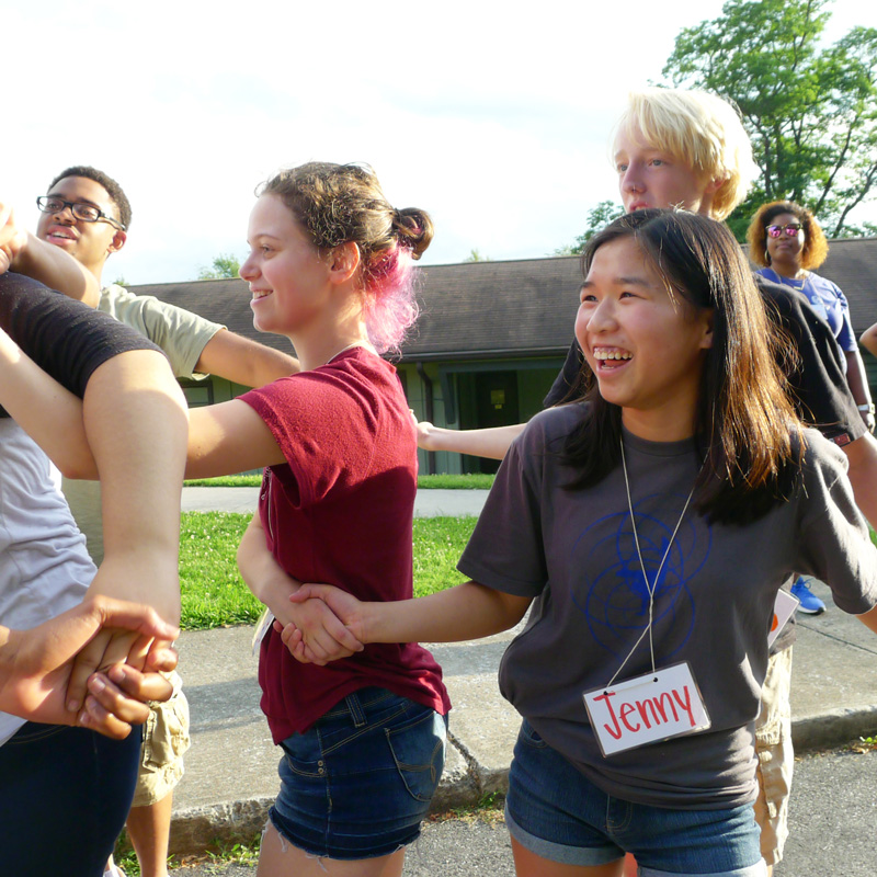 A group of multiethnic youth students interlocking hands in twisted standing positions while smiling.