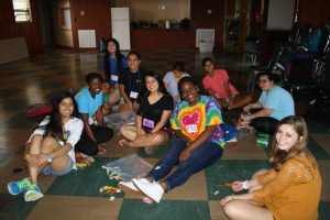 A group of multiracial youth students gathered together smiling in a group sitting on the floor doing crafts.