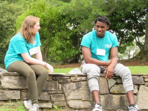 Two young people (one Black, one white) are sitting on a stone wall and having a serious conversation.
