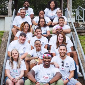 A group of multiracial adults sitting and smiling on steps wearing the same white shirt outdoors.