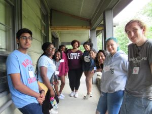A group of multiracial youth students gathered together in an outside hallway.
