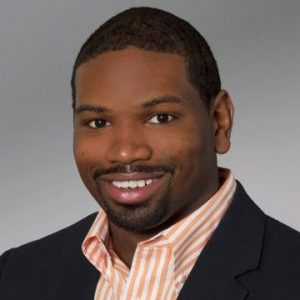An African American man wearing a black suit with an orange striped undershirt in front of a grey background.