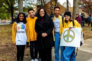 A group of multiracial adults and students smiling close together outside as a teen girl holds up a peace poster.