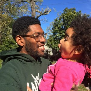 An African American man holding his younger daughter while smiling in front of trees.