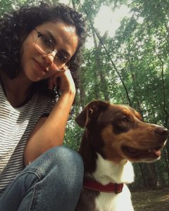 A Hispanic woman wearing black glasses smiling beside her brown dog outside in front of trees.