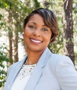 An African American woman wearing a light blue blazer and a white undershirt smiling outside in front of trees.