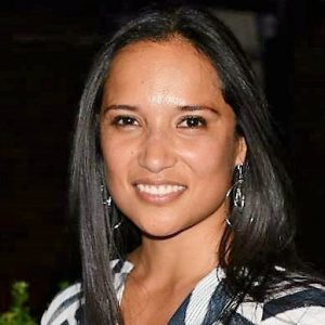 A Hispanic woman in a white and black patterned shirt smiling.