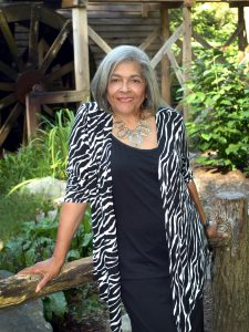 An African American woman wearing a zebra print cardigan and a black undershirt smiling outside, leaning on a wood log.