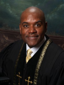 An African American man wearing a black and gold church robe smiling.