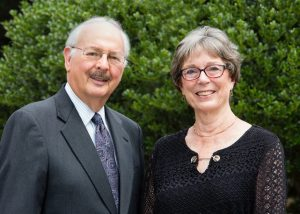 A White woman in a black dress and a White man in a grey suit smiling in front of a green bush.