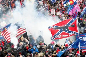 """A photograph of the capitol insurrection with hundreds of White adults in a crowd with smoke and various flags that says, """"Trump 2020,"""" """" Women for Trump,"""" and """"Come and Take it."""""""