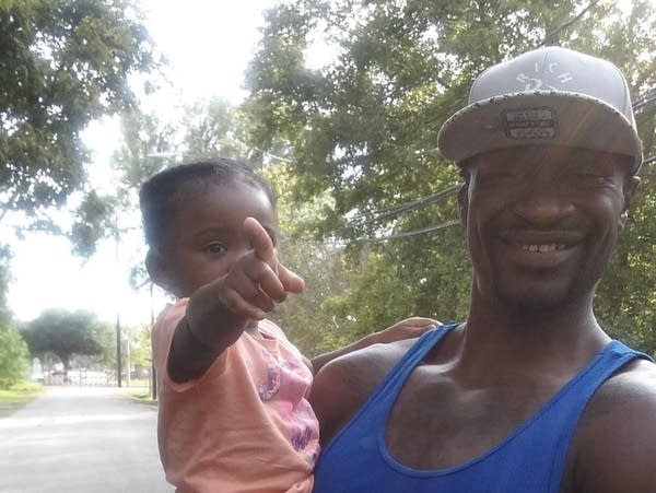 An African American man smiling and holding a baby girl while standing outdoors in front of trees.