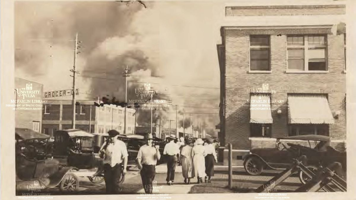 A older brown image of a town with brick buildings and older cars with smoke in the background.