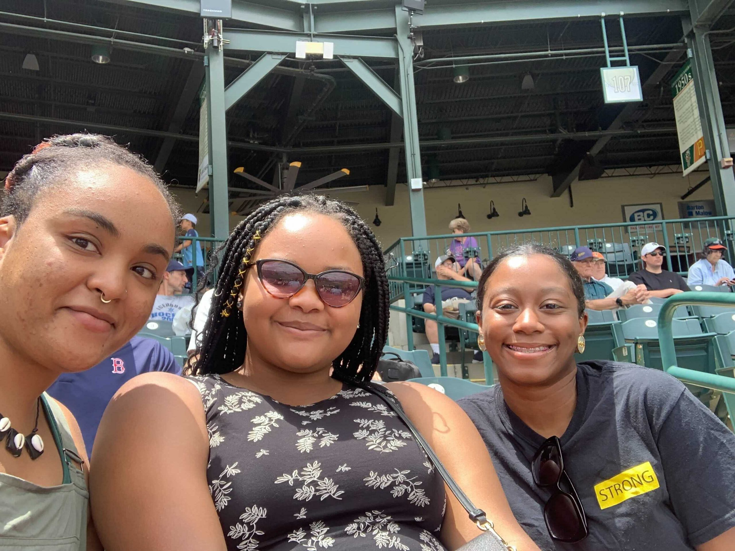 Three young Black women seated in a baseball stadium, taking a group selfie and smiling