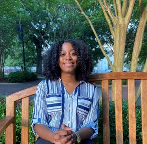 Young Black woman sitting on a park bench and smiling